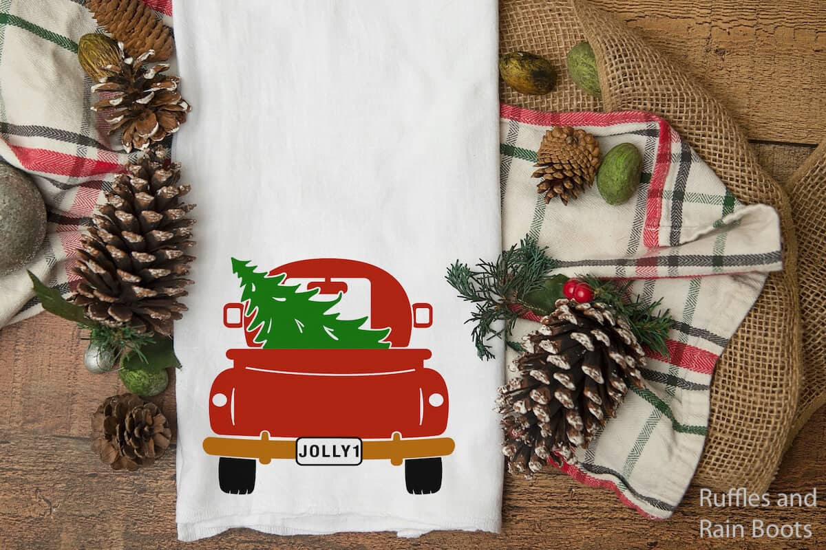 christmas farm truck svg collection on a kitchen towel on a wood table with winter items